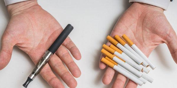 e-cigaret i én hånd, en håndfuld cigaretter i den anden